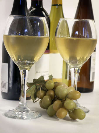 White wine in tall stem glasses with bottles at back, and grapes in between.