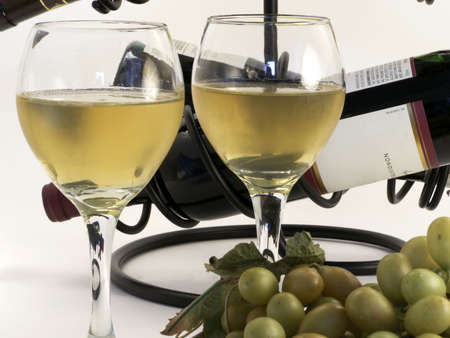 Close-up of wine in glasses with grapes in front and bottles at back. Standard-Bild