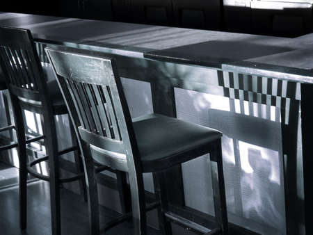 Vintage wooden bar stool casts shadow on bar in this blue-toned black & white shot. Standard-Bild