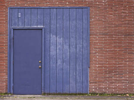 Blue door and frame in red brick wall.