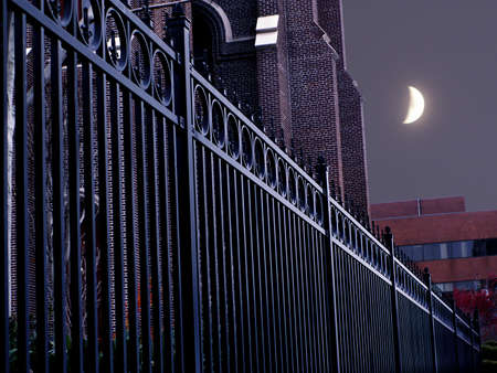 Light plays along rail of wrought iron fence in front of brick church with crescent moon rising. Standard-Bild