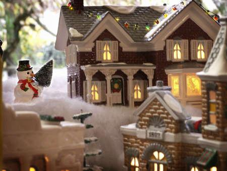 Snowman overlooks charming lights of Christmas villiage.