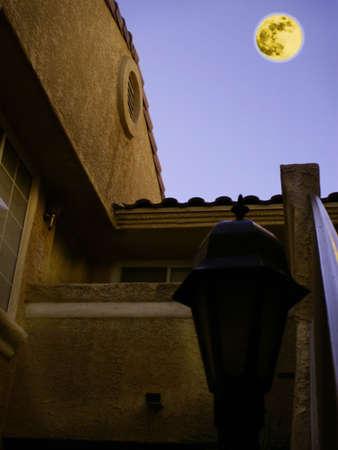 Adobe building in california desert lit by orange moon in purple sky. Standard-Bild