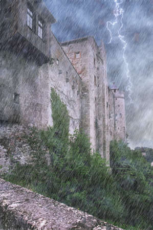 Rainy scene of massive castle walls with lightning in cloudy sky.