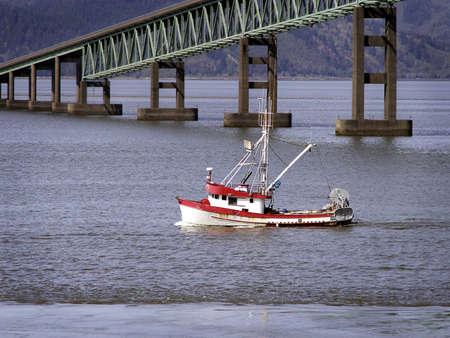 Red and white fishing trawler headed toward ocean, passing green river bridge. Standard-Bild