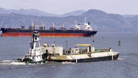 River barge pushed by tug passing ocean freighter at mouth of Columbia River. Standard-Bild