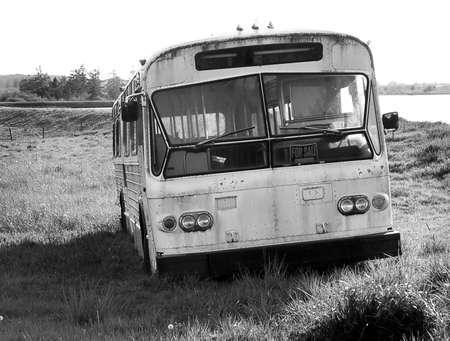 Aging bus sits vacant at the end of the line in this solitary black and white.