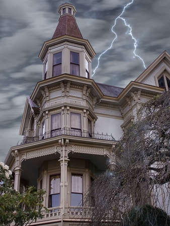 Stern looking victorian mansion weathers a lightening storm in this haunted feeling scene