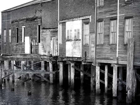 Old Mill buildings stand vacant on river pilings as water laps beneath in this lonely black & white image. Standard-Bild