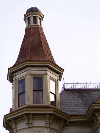 Vintage Victorian turret tower with red shingle roof stands starkly against the afternoon sky. Standard-Bild