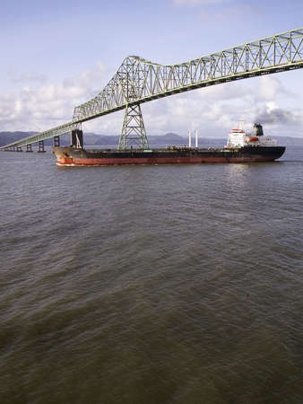 Ocean going freighter steams out to sea under Astoria bridge at mouth of Columbia River.