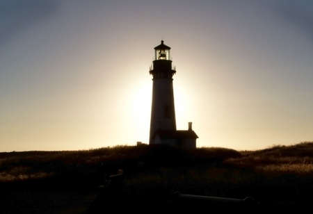 Silhouette of Oregon lighthouse at sunset.