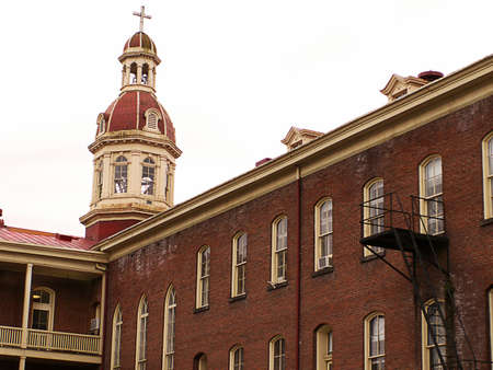 Architectural study of old (1870) red brick academy building with cupola and cross.