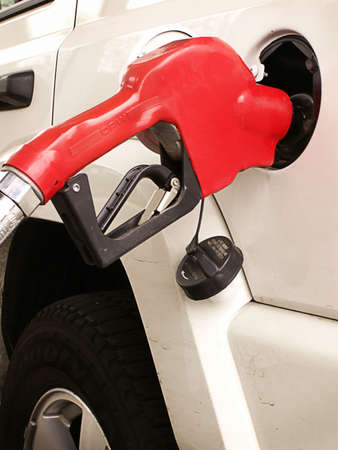 At the gas pump, the red handle of the gas line stands out against white SUV.