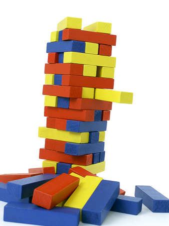 Colorful block tower leans to the right as one yellow block extends from stack, isolated on white background. Standard-Bild