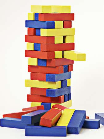 Block tower game with one yellow block protruding.