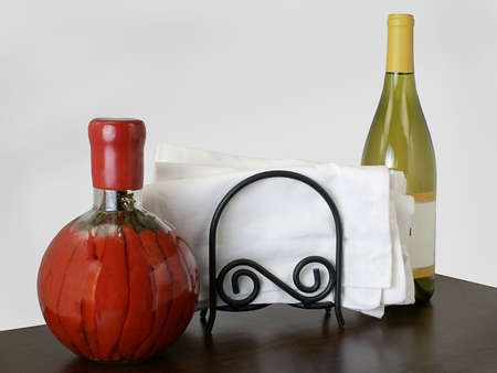Bottle with red chili peppers, cloth napkin holder, and bottle of white wine sit on wooden table in restaurant, against neutral wall.
