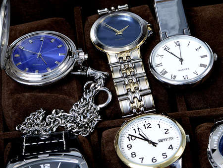 Close-up of mens watches including pocket watches and wrist watches.