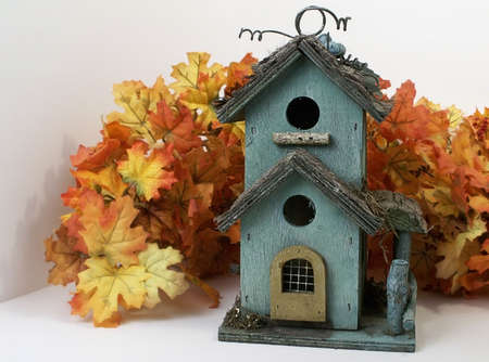 Weathered green birdhouse nestled in orange fall leaves.