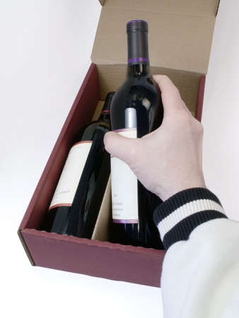 Mans hand removes bottle of red wine from shipping box.