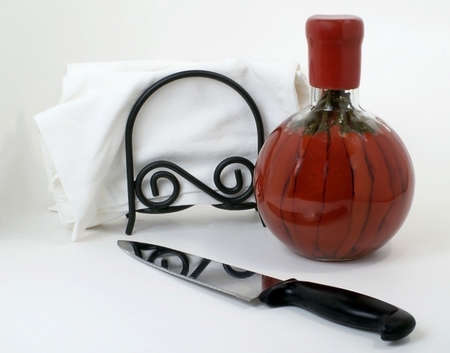 Still life of knife, cloth napkins, and bottle of red chilis, isloated on white.