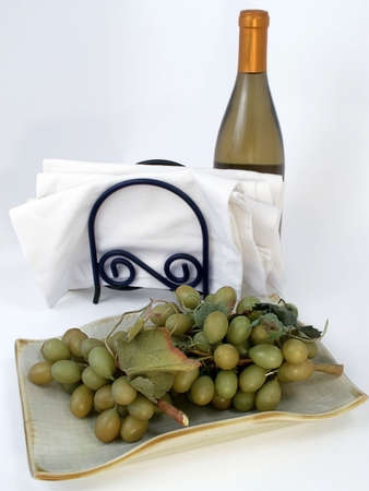 Plate of green grapes with white cloth napkins and bottle of white wine on neutral background.