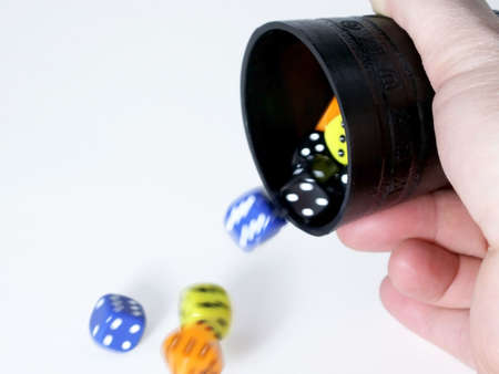 Colorful dice thrown from black cup tumble onto table, isolated on white background.