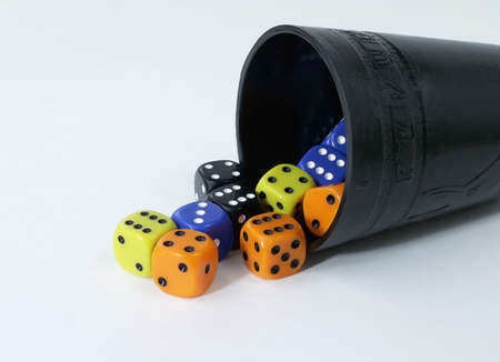 Black dice cup with multi-colored dice spilling out onto white background. Standard-Bild