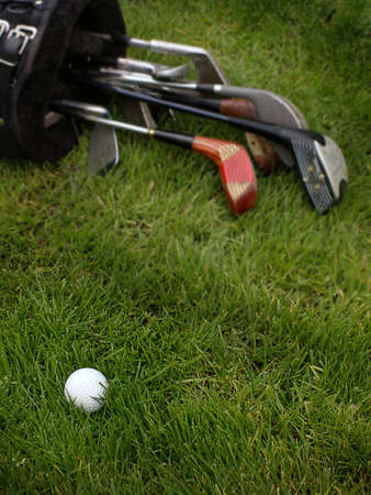 Golf ball lays in rough grass with older set of clubs in bag behind.