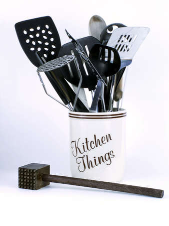 Jar of Kitchen Things with spatulas, wooden spoons, and other implements including wooden meat tenderizer in front, isolated on white background