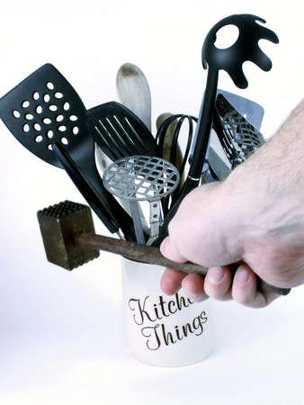 Mans hand grasps wooden meat tenderizer, with kitchen utensils in background.