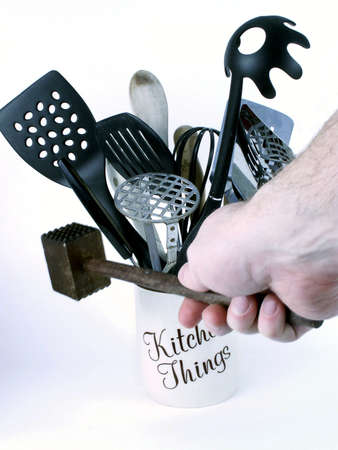 Man's hand grasps wooden meat tenderizer, with kitchen utensils in background.
