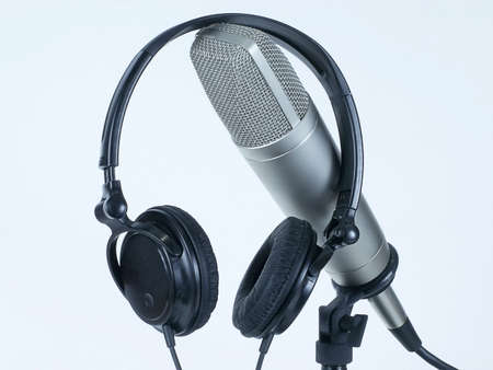 Headphone headset rests on professional studio cardioid microphone on table stand, isolated against white backround.