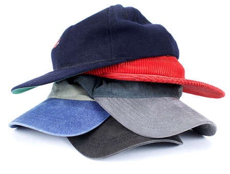 Stack of colorful mens, ball-style cloth hats isolated on white background.