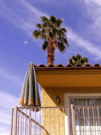 Tall Palm Tree rises above spanish style home with small terrace and umbrella table. Standard-Bild