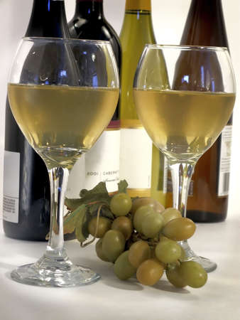 Two tall glasses of white wine with bunch of white grapes and bottles in background. Standard-Bild