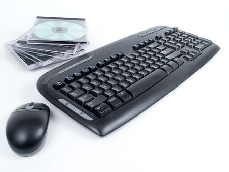 Black wireless keyboard and mouse with stack of CDs in cases, isolated on white background.