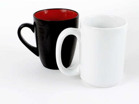 Two coffee mugs with different styles, one black, and one white isolated on white background.