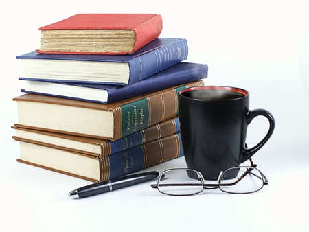 Stack of leather and hardback books with steaming coffee in mug, pen and glasses... ready to study.