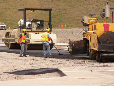 Road paving workers laying asphault with steam rollers at construction site.