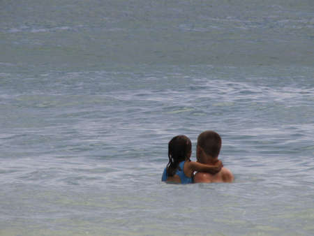 Father holds daughter in ocean at beach resort. Standard-Bild