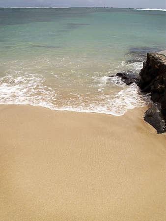 Warm green ocean rolls in on tropical beach.