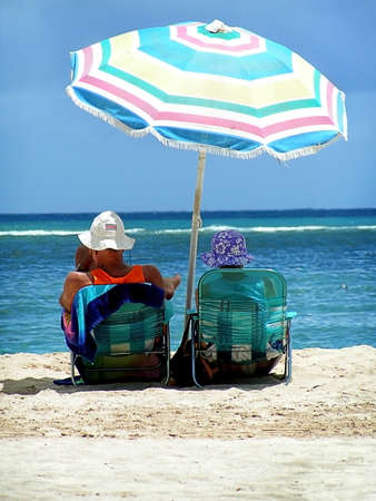 Older couple sit under umbrella on warm tropical beach.