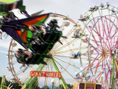 Energetic american fair/carnival scene with two rides in motion and one ferris wheel standing still.