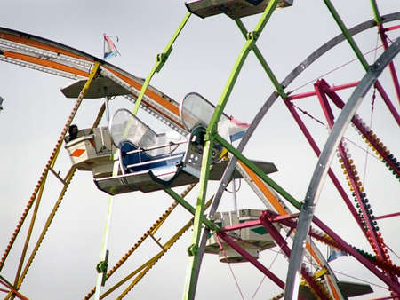 Intersecting ferris wheel rides, high in the air at carnival.