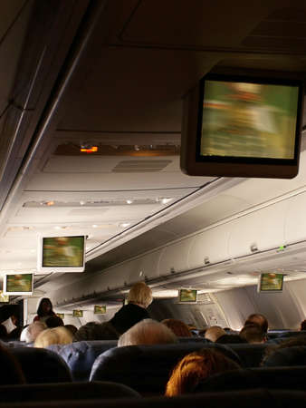 Stewardess serves passengers aboard jetliner as move plays on overhead monitors in cabin.