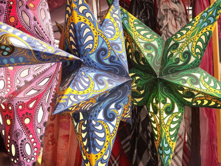 Colorful hand made star mobiles in shop at open air market.