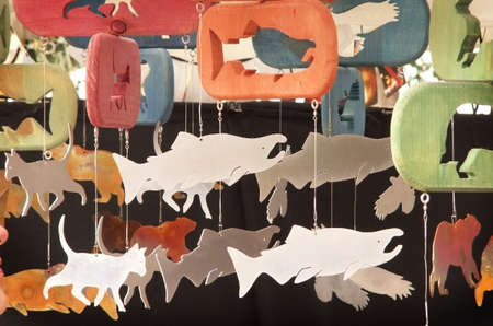 Colorful mobiles with animal shapes hang in marketplace.