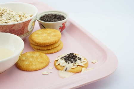 sweetened: Cracker, oat, chocolate and  sweetened condensed milk placed on a pink plate  Stock Photo
