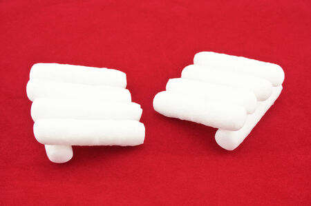 cushioning: Foam shape as cylinder  placed like hand on red background. Stock Photo